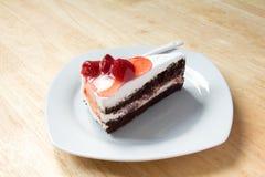 Κέικ φραουλών με το άσπρο πιάτο στο ξύλινο υπόβαθρο Στοκ Εικόνες