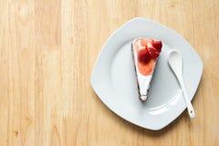 Κέικ φραουλών με το άσπρο πιάτο στο ξύλινο υπόβαθρο Στοκ Φωτογραφίες