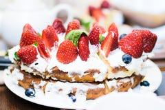 Κέικ φραουλών στα φύλλα κρέμας και μεντών στον πίνακα σε ένα πιάτο στοκ φωτογραφίες