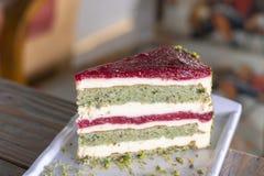 Κέικ φυστικιών και μούρων στο άσπρο πιάτο στοκ φωτογραφίες με δικαίωμα ελεύθερης χρήσης