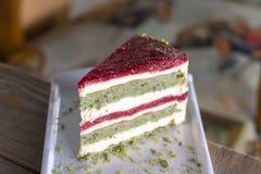 Κέικ φυστικιών και μούρων στο άσπρο πιάτο στοκ εικόνα