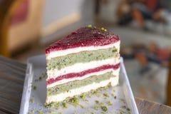 Κέικ φυστικιών και μούρων στο άσπρο πιάτο στοκ φωτογραφία