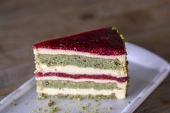 Κέικ φυστικιών και μούρων στο άσπρο πιάτο στοκ εικόνα με δικαίωμα ελεύθερης χρήσης