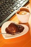 Κέικ φλιτζανιών του καφέ και σοκολάτας δίπλα στον υπολογιστή Στοκ εικόνες με δικαίωμα ελεύθερης χρήσης