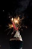 Κέικ φλυτζανιών με τα κεριά πυροτεχνημάτων και γενεθλίων Στοκ Εικόνες