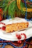 Κέικ Χριστουγέννων στο άσπρο πιάτο με τα παιχνίδια δέντρων και Χριστουγέννων γουνών Στοκ Εικόνα