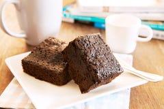 Κέικ Browny έτοιμο να φάει στο άσπρο πιάτο με το φλυτζάνι καφέ και magaz Στοκ Εικόνες