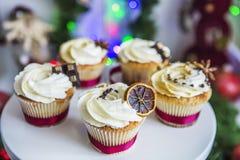 Κέικ, cupcakes με το ξηρές λεμόνι και τη σοκολάτα σε ένα άσπρο βάθρο σε ένα υπόβαθρο της πράσινης γιρλάντας και των φω'των Χριστο Στοκ Εικόνες