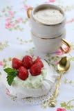 Κέικ Pavlova με τις φράουλες με ένα φλυτζάνι του cappuccino σε μια ζωηρόχρωμη πετσέτα Στοκ Φωτογραφία