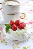 Κέικ Pavlova με τις φράουλες με ένα φλυτζάνι του cappuccino σε μια ζωηρόχρωμη πετσέτα Στοκ φωτογραφίες με δικαίωμα ελεύθερης χρήσης
