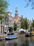 Κέντρο του Άμστερνταμ - Oudezijds Voorburgwal - σπίτια καναλιών με τον πύργο Oude Kerk Στοκ Εικόνα