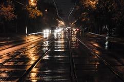 Κέντρο του δρόμου με τις ράγες Η πόλη νύχτας με την κυκλοφορία νύχτας κάτω από τη βροχή στοκ εικόνες