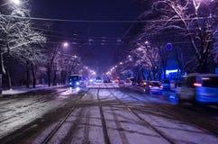 Κέντρο του χιονώδους δρόμου με τα τραμ Η πόλη νύχτας με την κυκλοφορία νύχτας στοκ εικόνες