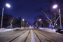Κέντρο του χιονώδους δρόμου με τις ράγες Η πόλη νύχτας με την κυκλοφορία νύχτας στοκ εικόνες
