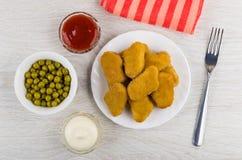 Κέτσαπ, μαγιονέζα, πράσινα μπιζέλια, ψήγματα κοτόπουλου, δίκρανο, πετσέτα στοκ εικόνες