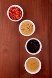 Κέτσαπ σαλτσών, μουστάρδα, μαγιονέζα, ξινή κρέμα, σάλτσα σόγιας στα κύπελλα αργίλου στο ξύλινο υπόβαθρο Τοπ όψη Στοκ Εικόνα