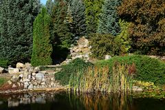 Κήπος φθινοπώρου με την τεχνητή λίμνη και το στεγνωμένο καταρράκτη πετρών που απεικονίζουν στην επιφάνεια νερού Στοκ εικόνες με δικαίωμα ελεύθερης χρήσης