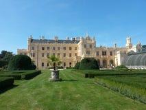 Κήπος Lednice του Castle στην ηλιόλουστη ημέρα με το κάστρο και θερμοκήπιο στο υπόβαθρο στοκ εικόνα