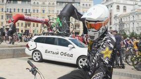 Κίεβου/επάνω Ουκρανία-Ιουνίου, 1 του 2019 στενός του ποδηλάτη βουνών στην πορτοκαλιά μάσκα και το μεγάλο άσπρο κράνος που κοιτάζο απόθεμα βίντεο