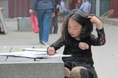 Κίνα, Suzhou - 14 Απριλίου 2012 Ένα κινεζικό κορίτσι σύρει σε ένα βιβλίο ο Στοκ Φωτογραφίες