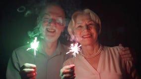 κίνηση αργή Ανώτερο ζεύγος με τα sparklers που γιορτάζει τα Χριστούγεννα Ευτυχή φω'τα της Βεγγάλης οικογενειακής εκμετάλλευσης φιλμ μικρού μήκους