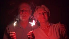 κίνηση αργή Ανώτερο ζεύγος με τα sparklers που γιορτάζει τα Χριστούγεννα Ευτυχή φω'τα της Βεγγάλης οικογενειακής εκμετάλλευσης απόθεμα βίντεο