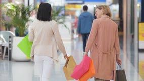 κίνηση αργή Δύο ευτυχείς νέες γυναίκες που περπατούν στη λεωφόρο αγορών με τις τσάντες αγορών φιλμ μικρού μήκους