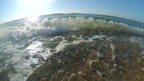 κίνηση αργή Κύμα θάλασσας με τους άσπρους ρόλους αφρού στην αμμώδη παραλία απόθεμα βίντεο