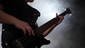 κίνηση αργή Μουσικός παιχνιδιού στη βαθιά κιθάρα τεσσάρων σειρών closeup φιλμ μικρού μήκους