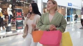 κίνηση αργή Ψωνίζοντας γυναίκες που μιλούν τις ευτυχείς τσάντες αγορών εκμετάλλευσης που έχουν το γέλιο διασκέδασης όμορφες δύο ν απόθεμα βίντεο