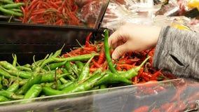 Κίνηση γυναικών ` του μαζέματος με το χέρι του s πράσινου και του κοκκίνου - καυτό πιπέρι μέσα σε Superstore φιλμ μικρού μήκους
