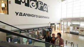 Κίνηση κάτω από τις χαμογελώντας γυναίκες παρελθόντος στην κυλιόμενη σκάλα στη λεωφόρο απόθεμα βίντεο