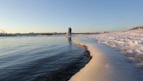 Κίνηση καμερών κατά μήκος της παγωμένης ακτής στο αγκάλιασμα της νύφης και του νεόνυμφου απόθεμα βίντεο
