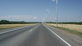 Κίνηση κατά μήκος του δρόμου ασφάλτου προς τον ορίζοντα με τα δέντρα και τον ουρανό απόθεμα βίντεο