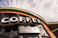 Κίνηση καφέ μέσω του σημαδιού με το νεφελώδη ουρανό στοκ εικόνες