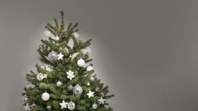 Κίνηση στάσεων των άσπρων και ασημένιων εορταστικών διακοσμήσεων μόνος-που τελειώνουν ένα χριστουγεννιάτικο δέντρο απόθεμα βίντεο