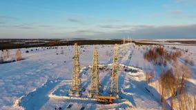 Κίνηση στους πύργους υψηλής τάσης μεταξύ του χιονιού ενάντια στον ουρανό φιλμ μικρού μήκους