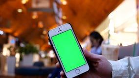 Κίνηση της γυναίκας που κρατά το πράσινο τηλέφωνο οθόνης με τους ανθρώπους θαμπάδων που ψωνίζουν και που στηρίζονται απόθεμα βίντεο