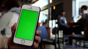 Κίνηση της γυναίκας που κρατά το πράσινο τηλέφωνο οθόνης με τους ανθρώπους θαμπάδων που πίνουν τον καφέ απόθεμα βίντεο