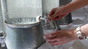 Κίνηση της γυναίκας που παίρνει ένα φλυτζάνι του νερού από την πιό δροσερή δεξαμενή νερού φιλμ μικρού μήκους