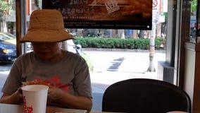 Κίνηση της γυναίκας που τρώει burger και που πίνει τον καυτό καφέ φιλμ μικρού μήκους