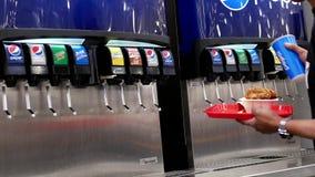 Κίνηση του ατόμου που επιλέγει το δροσερό ποτό πηγών από τη μηχανή σόδας αυτοεξυπηρετήσεων στην περιοχή δικαστηρίων τροφίμων Cost απόθεμα βίντεο