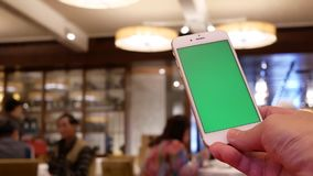Κίνηση του ατόμου που κρατά το πράσινο τηλέφωνο οθόνης με τους ανθρώπους θαμπάδων που τρώνε τα τρόφιμα και να κουβεντιάσει απόθεμα βίντεο