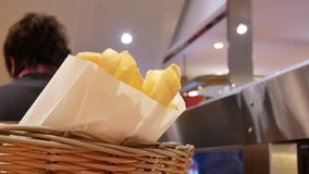 Κίνηση του ατόμου που τρώει τα τηγανητά στον πίνακα στο δικαστήριο τροφίμων απόθεμα βίντεο