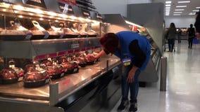 Κίνηση του εργαζομένου που βάζει το καυτό καρυκευμένο κοτόπουλο στο ράφι φούρνων επίδειξης για την πώληση απόθεμα βίντεο