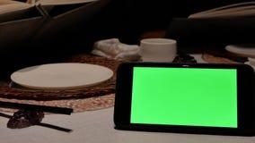 Κίνηση του πράσινου τηλεφώνου οθόνης με τους ανθρώπους θαμπάδων που εξετάζουν τις επιλογές απόθεμα βίντεο