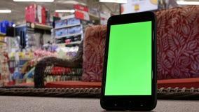 Κίνηση του πράσινου τηλεφώνου οθόνης μπροστά από τον καναπέ επίδειξης απόθεμα βίντεο