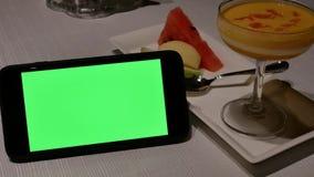 Κίνηση του πράσινων τηλεφώνου οθόνης και του επιδορπίου πουτίγκας μάγκο απόθεμα βίντεο