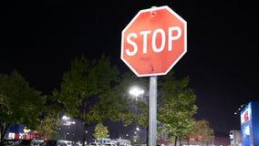 Κίνηση του σημαδιού στάσεων μπροστά από το χώρο στάθμευσης στη βρέχοντας νύχτα απόθεμα βίντεο