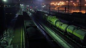 Κίνηση τριών φορτηγών τρένων στο σιδηρόδρομο στη χειμερινή νύχτα απόθεμα βίντεο